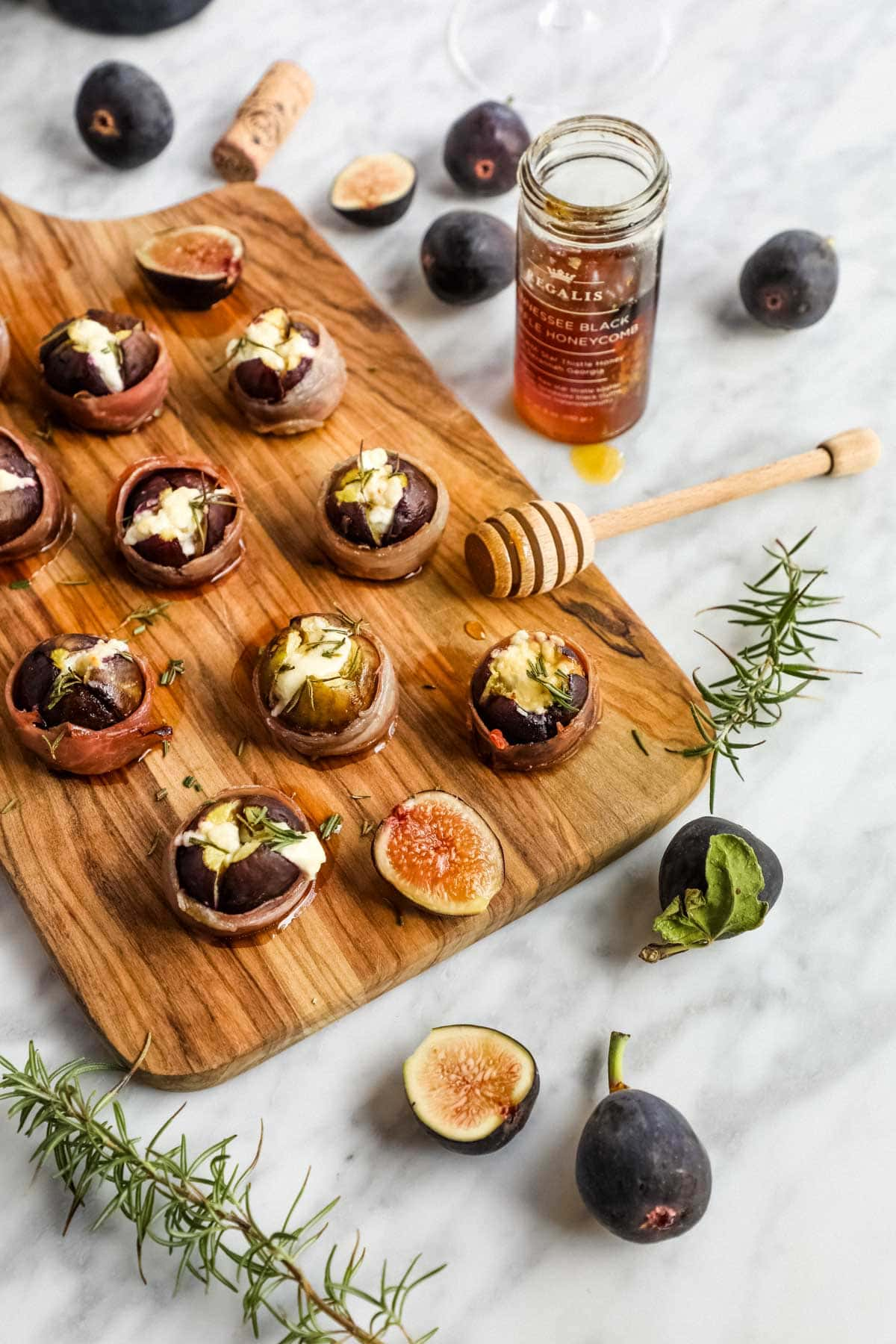 Prosciutto Wrapped Figs with Goat Cheese on cutting board with honey.
