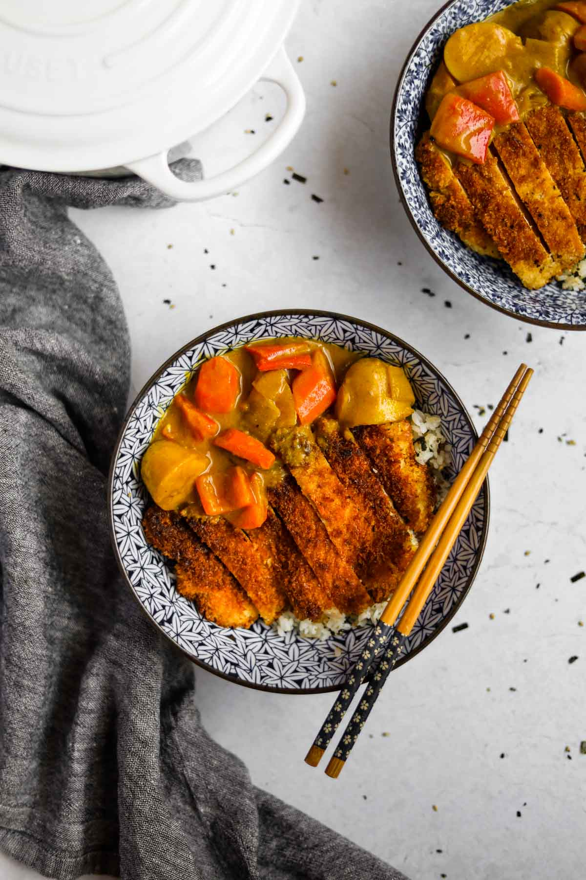 Chicken Katsu Curry in blue Japanese bowl with chopsticks and dutch oven in an overhead shot