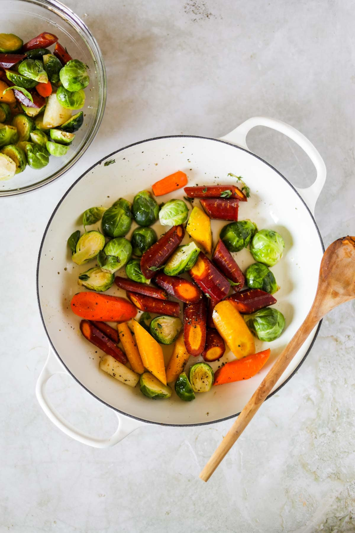 Brussel Sprouts and Carrots in a white Le Creuset braiser with a wooden spoon.