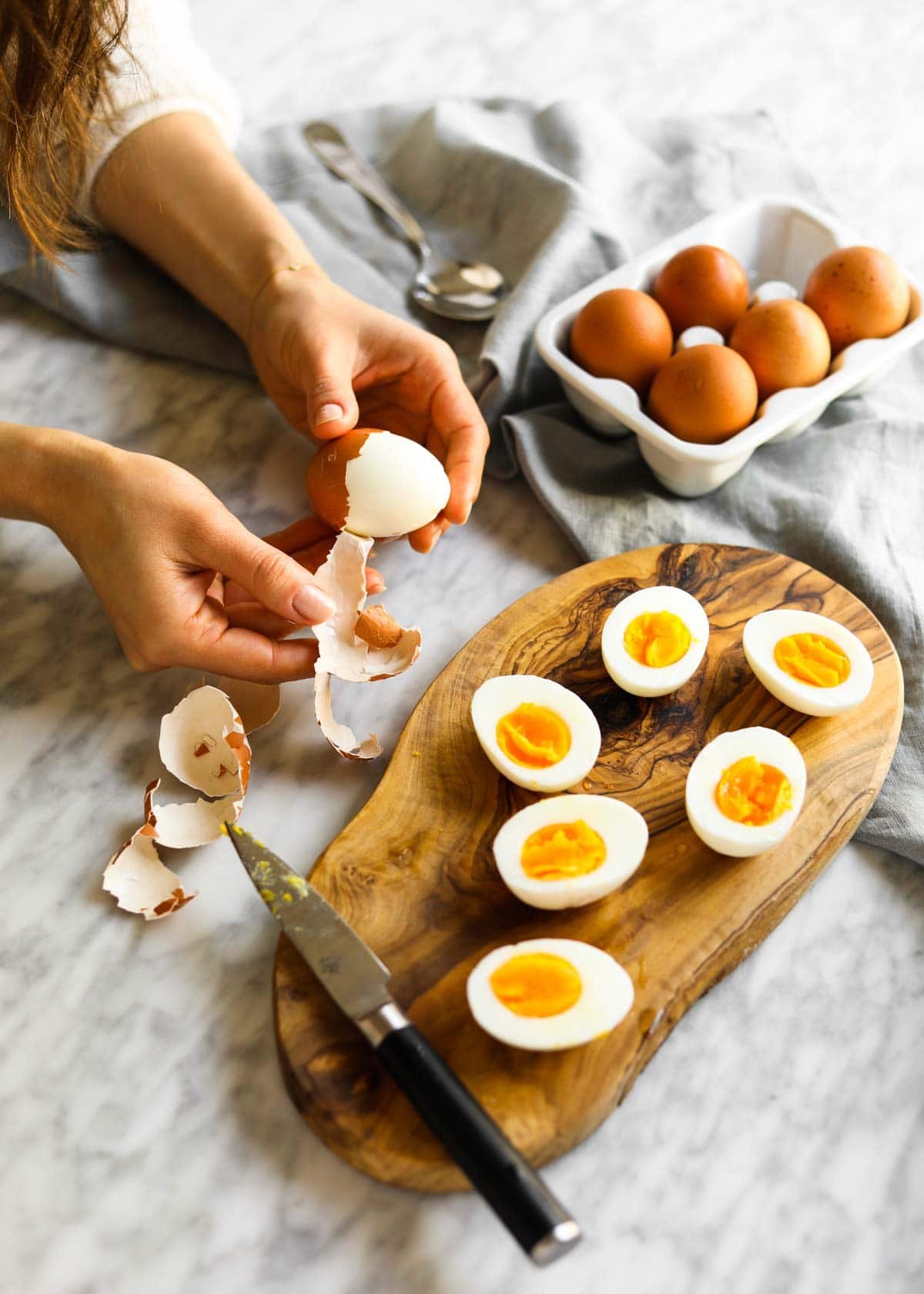 Soft boiled egg being peeled with peeled and cut soft boiled eggs on cutting board and knife.